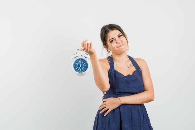 Young woman holding alarm clock in dress and looking confident