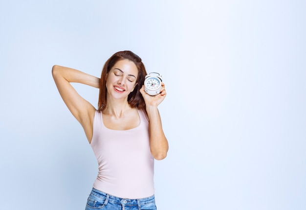 Young woman holding an alarm clock and feeling sleepy
