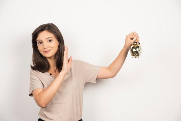 Молодая женщина, держащая будильник на белом фоне. Бесплатные Фотографии
