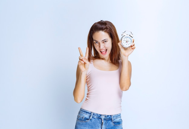 Young woman holding an alarm clock and pointing at it