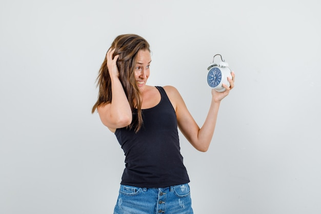 Young woman holding alarm clock in singlet, shorts and looking anxious. front view.