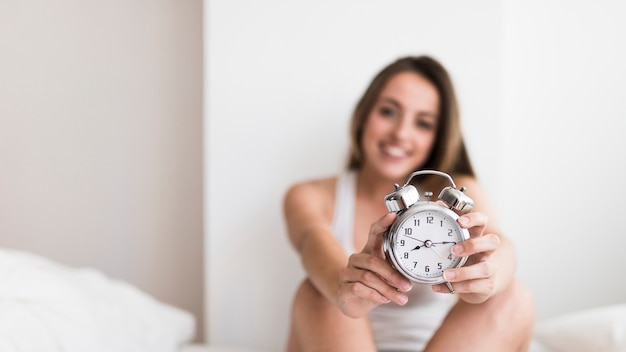 Young woman holding alarm clock