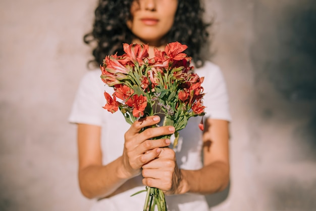Young woman holding alstroemeria red flower bouquet in hands