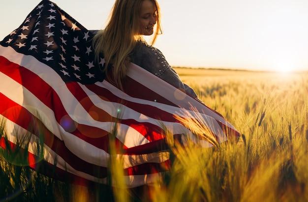 Молодая женщина, держащая американский флаг на закате