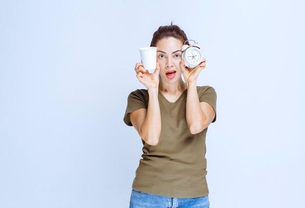 Молодая женщина держит будильник и чашку напитка, указывая на утреннюю рутину