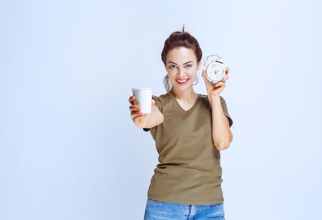 目覚まし時計と朝のルーチンを指している飲み物のカップを保持している若い女性