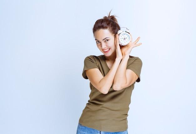 Молодая женщина держит будильник и выглядит довольной, так как никогда не опаздывает