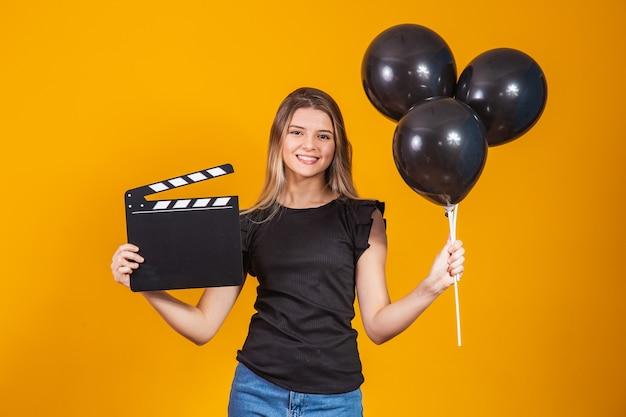 ブラックフライデーの間に視聴覚カチンコと黒い風船を持っている若い女性。プロモーションのコンセプト。ブラックフライデー