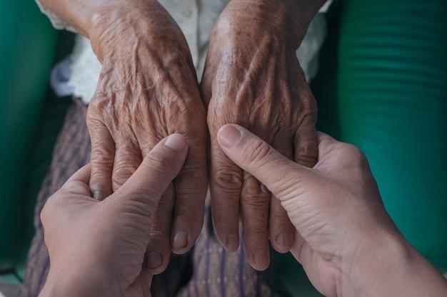 노인 여성의 손을 잡고하는 젊은 여자.