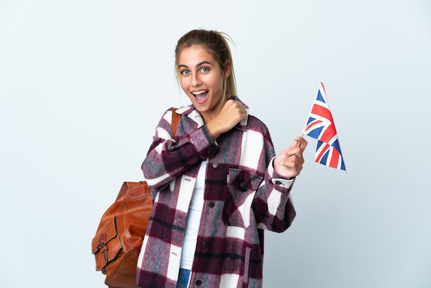 勝利を祝う白い壁に分離された英国の旗を保持している若い女性