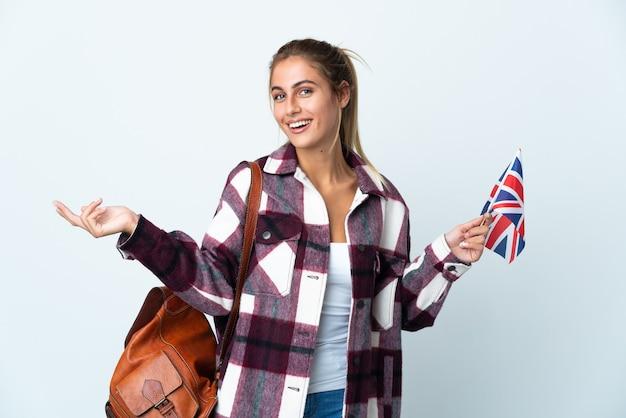 白い壁に隔離された英国の旗を持って若い女性が来て招待するために手を横に伸ばします