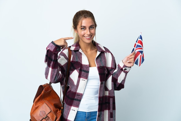 親指を立てるジェスチャーを与える白い壁に分離された英国の旗を保持している若い女性