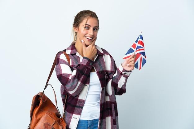 幸せと笑顔で白い壁に分離された英国旗を保持している若い女性