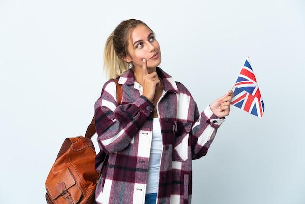 見上げている間疑いを持っている白い壁に分離された英国の旗を保持している若い女性