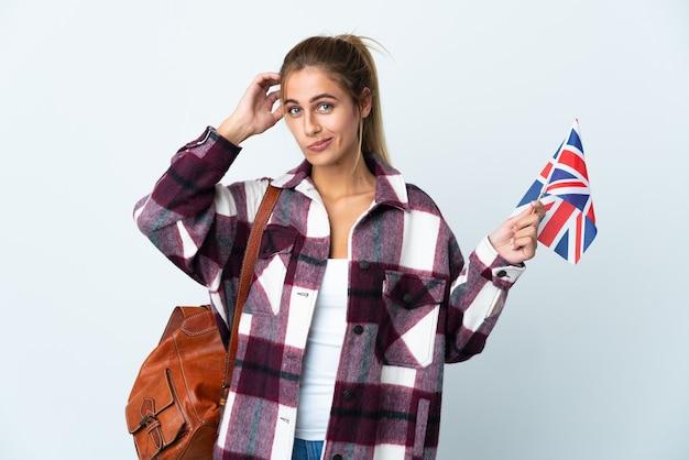 疑いを持って白い壁に分離された英国の旗を保持している若い女性