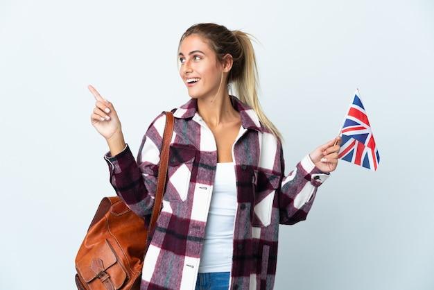 指を持ち上げながら解決策を実現しようとしている白い壁に分離された英国の旗を保持している若い女性