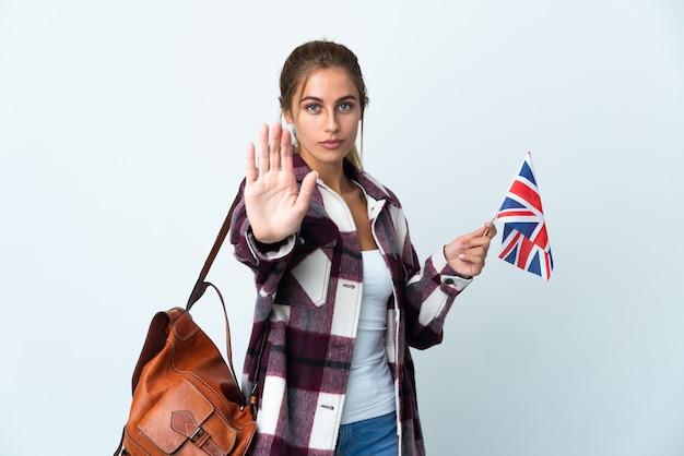 停止ジェスチャーを作る白い壁に分離された英国の旗を保持している若い女性