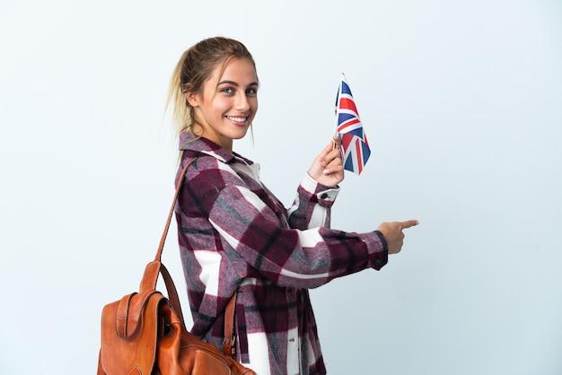後ろ向きの白い壁に分離された英国の旗を保持している若い女性