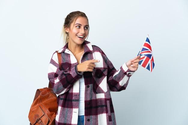 横に指を指し、製品を提示する白い壁に分離された英国の旗を保持している若い女性