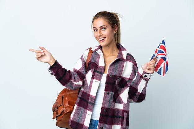 横に指を指している白い壁に分離された英国の旗を保持している若い女性