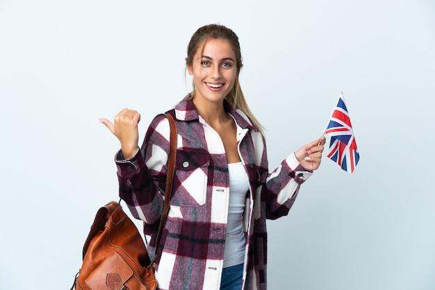製品を提示する側を指している白い壁に分離された英国の旗を保持している若い女性