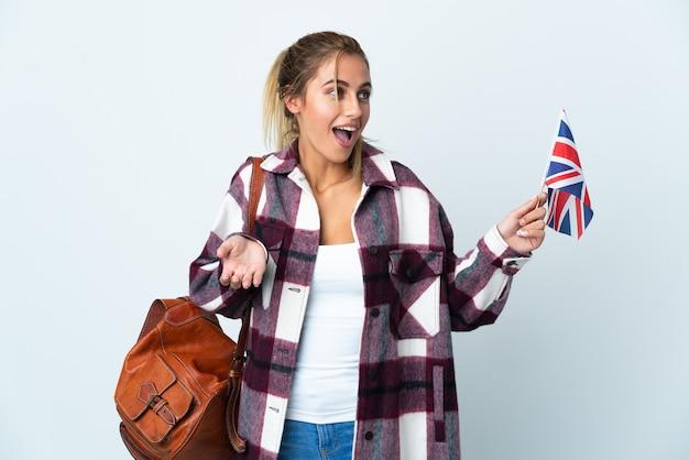 側面を見ながら驚きの表情で白い壁に分離された英国旗を保持している若い女性