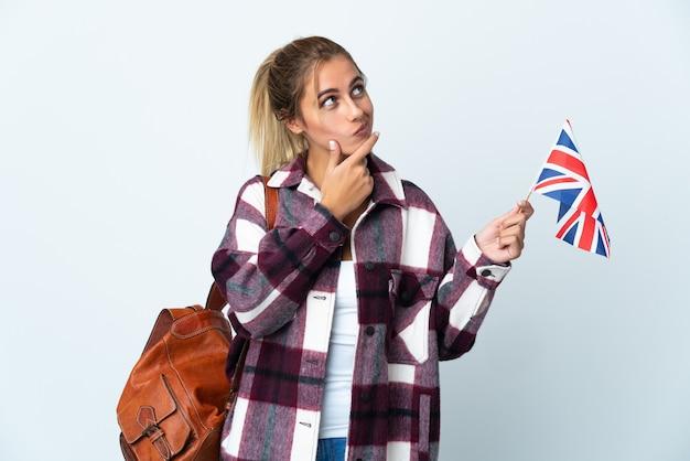疑いを持って白で英国旗を保持している若い女性