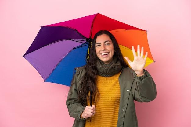 Молодая женщина, держащая зонтик на розовом фоне, считая пять пальцами