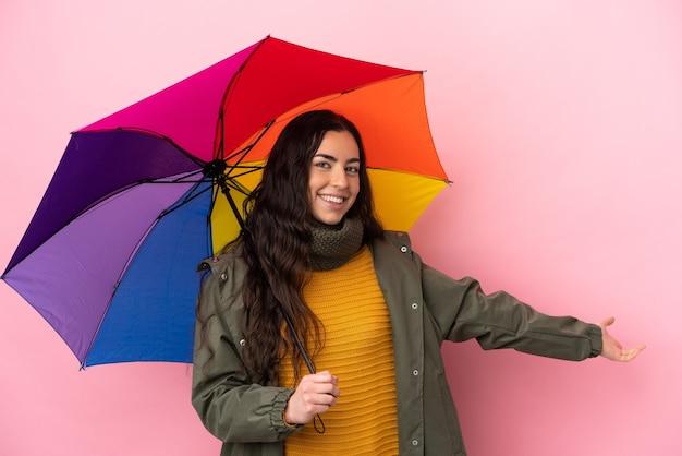 Молодая женщина, держащая зонтик, изолированная на розовом фоне, протягивает руки в сторону, приглашая приехать