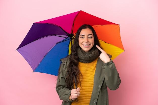 Молодая женщина, держащая зонтик, изолированная на розовом фоне, показывая жест пальца вверх