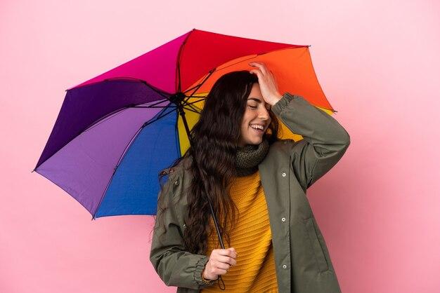 분홍색 배경에 고립 된 우산을 들고 젊은 여자가 뭔가를 실현하고 해결책을 계획하고 있습니다