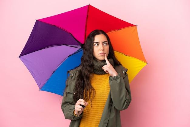 Молодая женщина, держащая зонтик, изолированная на розовом фоне, сомневается, глядя вверх