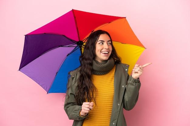 분홍색 배경에 고립 된 우산을 들고 젊은 여자는 손가락을 들어 올리는 동안 솔루션을 실현하려는 의도
