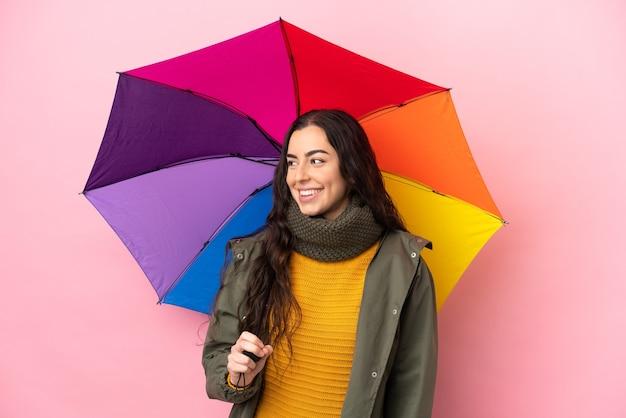 Молодая женщина, держащая зонтик, изолированная на розовом фоне, смотрящая сторона