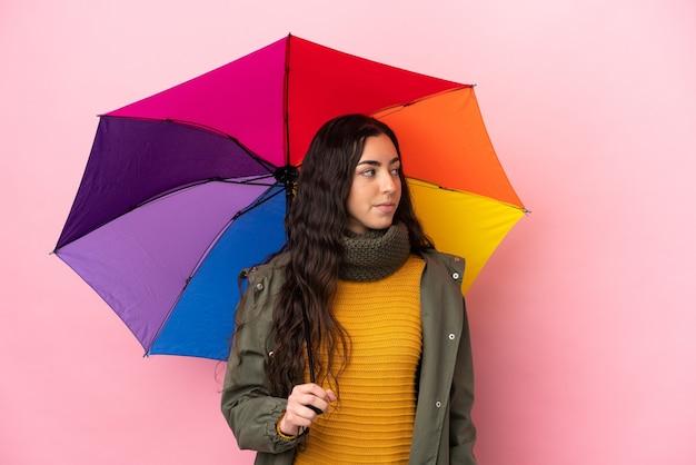 Молодая женщина, держащая зонтик на розовом фоне, глядя в сторону
