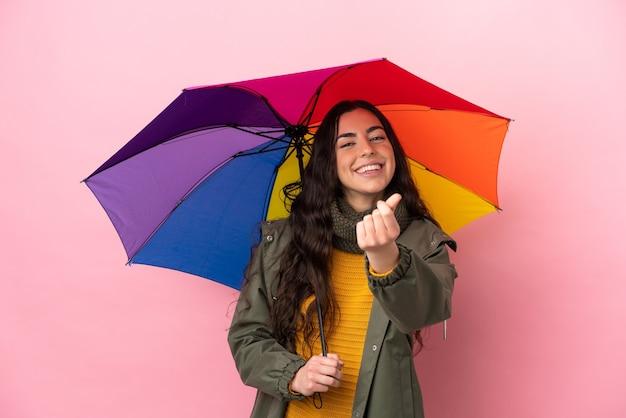 Молодая женщина, держащая зонтик, изолированные на розовом фоне, делая денежный жест