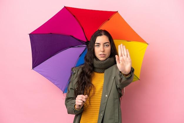 중지 제스처를 만드는 분홍색 배경에 고립 된 우산을 들고 젊은 여자