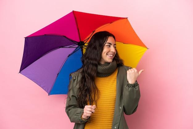 제품을 제시하기 위해 측면을 가리키는 분홍색 배경에 고립 된 우산을 들고 젊은 여자