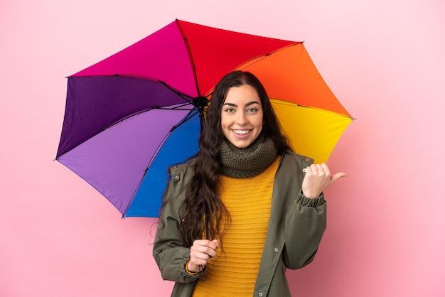 Молодая женщина, держащая зонтик на розовом фоне, указывая в сторону, чтобы представить продукт