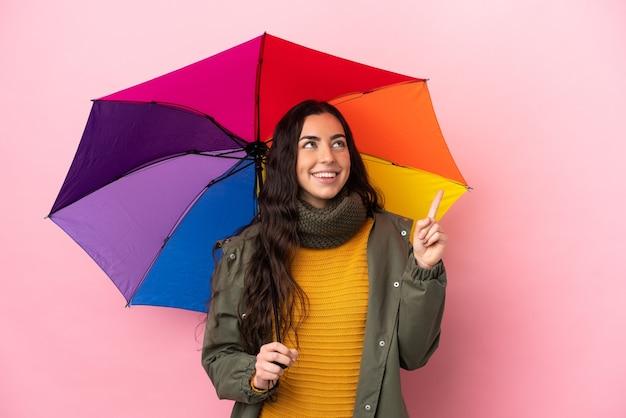 좋은 아이디어를 가리키는 분홍색 배경에 고립 된 우산을 들고 젊은 여자
