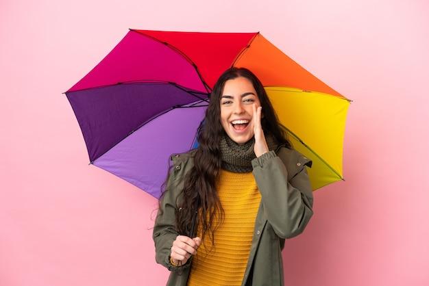 입 벌리고 외치는 분홍색 배경에 고립 된 우산을 들고 젊은 여자