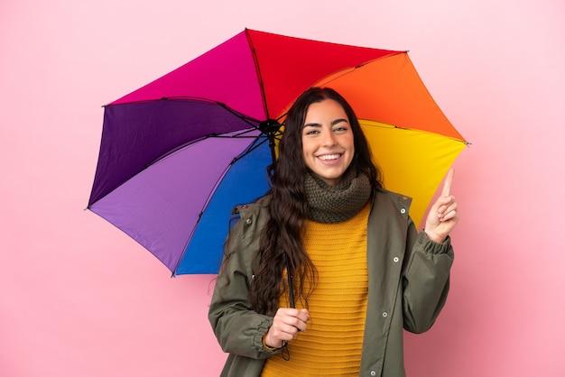 Молодая женщина, держащая зонтик на розовом фоне, показывает и поднимает палец в знак лучших