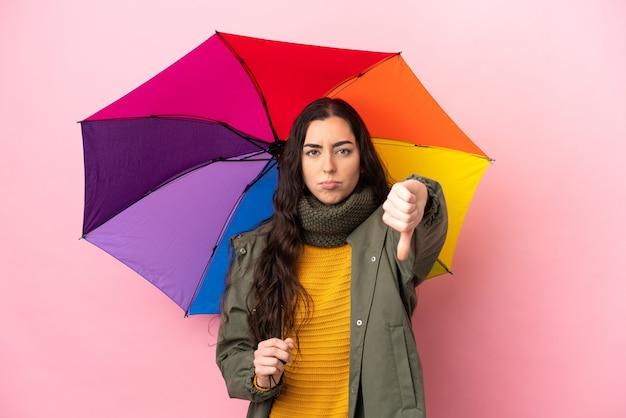 부정적인 표현으로 아래로 엄지 손가락을 보여주는 분홍색 배경에 고립 된 우산을 들고 젊은 여자