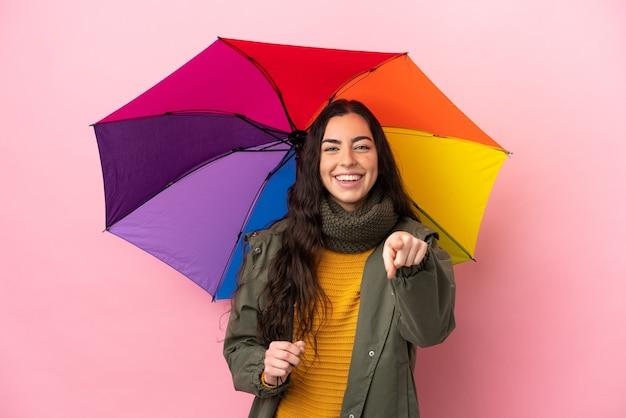 Молодая женщина, держащая зонтик, изолированная на розовом фоне, удивилась и указала спереди