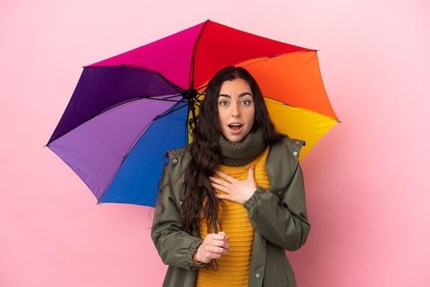 ピンクの背景に分離された傘を持っている若い女性は、右を見ながら驚いてショックを受けました