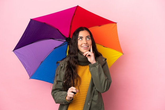 Молодая женщина, держащая зонтик, изолированная на розовом фоне, думает об идее, глядя вверх