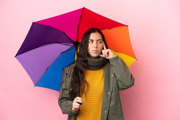 아이디어를 생각하는 분홍색 배경에 고립 된 우산을 들고 젊은 여자