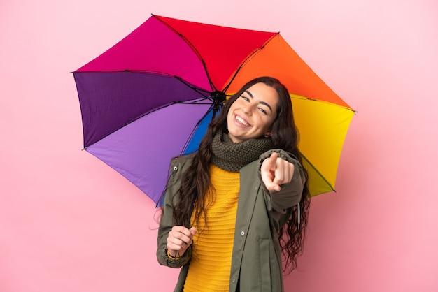 Молодая женщина, держащая зонтик, изолированная на розовой стене, указывая вперед с счастливым выражением лица