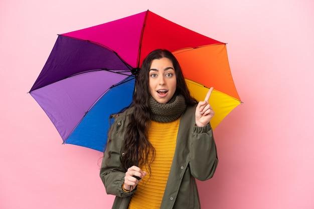Молодая женщина, держащая зонтик, изолированная на розовой стене, думает о идее, указывая пальцем вверх