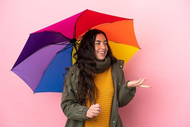 Молодая женщина, держащая зонтик, изолированная на розовой стене с удивленным выражением лица, глядя в сторону